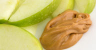 Green apple slices on dish with peanut butter close view