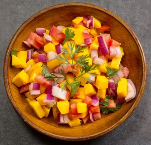Homemade Mango salsa served in a wooden plate top view