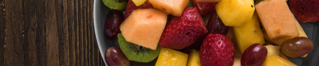Plate full of healthy exotic fruits slices, from above on wooden table