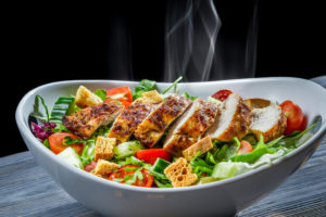 Hot chicken and fresh vegetables in healthy salad.